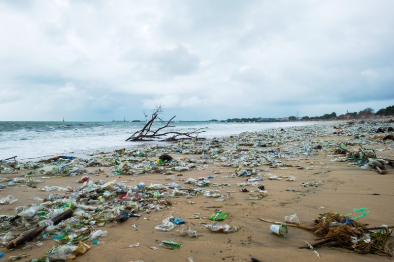 Garbage on beach, environmental pollution in Bali Indonesia. Drops of water are on camera lens. Dramatic view