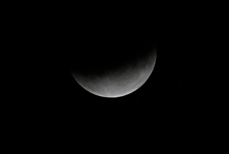 The moon is seen during a lunar eclipse above the town of Rafah on the southern Gaza Strip, on July 17, 2019. (Photo by SAID KHATIB / AFP)