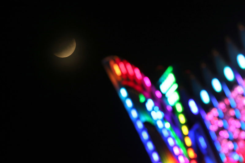 16 July 2019, Bavaria, Würzburg: The moon is visible during a partial lunar eclipse behind a ride of the Kiliani festival. Photo: Karl-Josef Hildenbrand/dpa