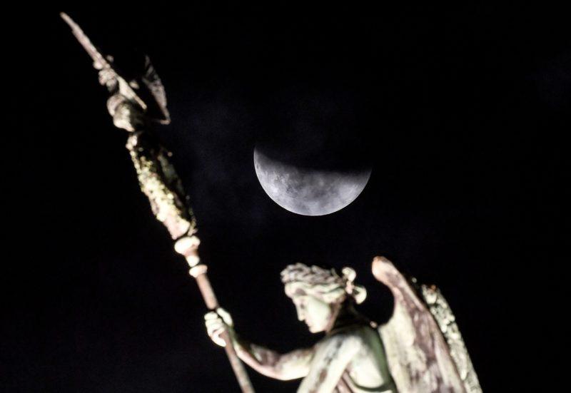 16 July 2019, Berlin: The moon can be seen during a partial lunar eclipse behind the quadriga of the Brandenburg Gate. Photo: Britta Pedersen/dpa-Zentralbild/dpa