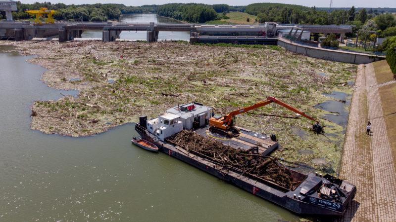 Kisköre, 2019. július 16. Uszályra rakodja a tavaszi árhullámokat követõen összetorlódott mintegy nyolcezer tonna kommunális és növényi eredetû hulladékot egy munkagép a kiskörei vízlépcsõnél 2019. július 16-án. Vízügyi, civil és vállalati együttmûködés segíti a Tisza hulladékmentesítését, az idén rekordméretû szennyezés felszámolása legalább négy hónapot vesz majd igénybe. MTI/Czeglédi Zsolt