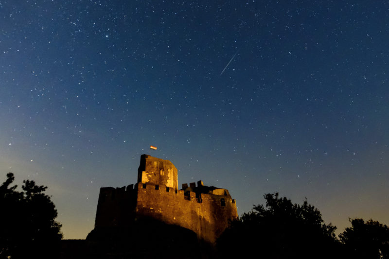 Hollókõ, 2019. augusztus 12. Meteor az égbolton a hollókõi vár felett 2019. augusztus 12-re virradóan. A Föld belépett a Perseida meteorraj összetevõit alkotó 109P/Swift-Tuttle üstökös pályája mentén szétszórt porfelhõbe. A Perseidák az egyik legismertebb, sûrû csillaghullást elõidézõ meteorraj. MTI/Komka Péter