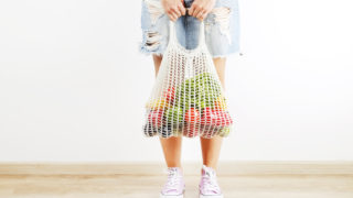 Young woman in plaid shirt, jeans skirt with bag of mixed fruit, vegetables & greens: corn cob, tomato, pepper, lettuce, pear & apple. Zero waste concept. Copy space background, wooden floor, close up