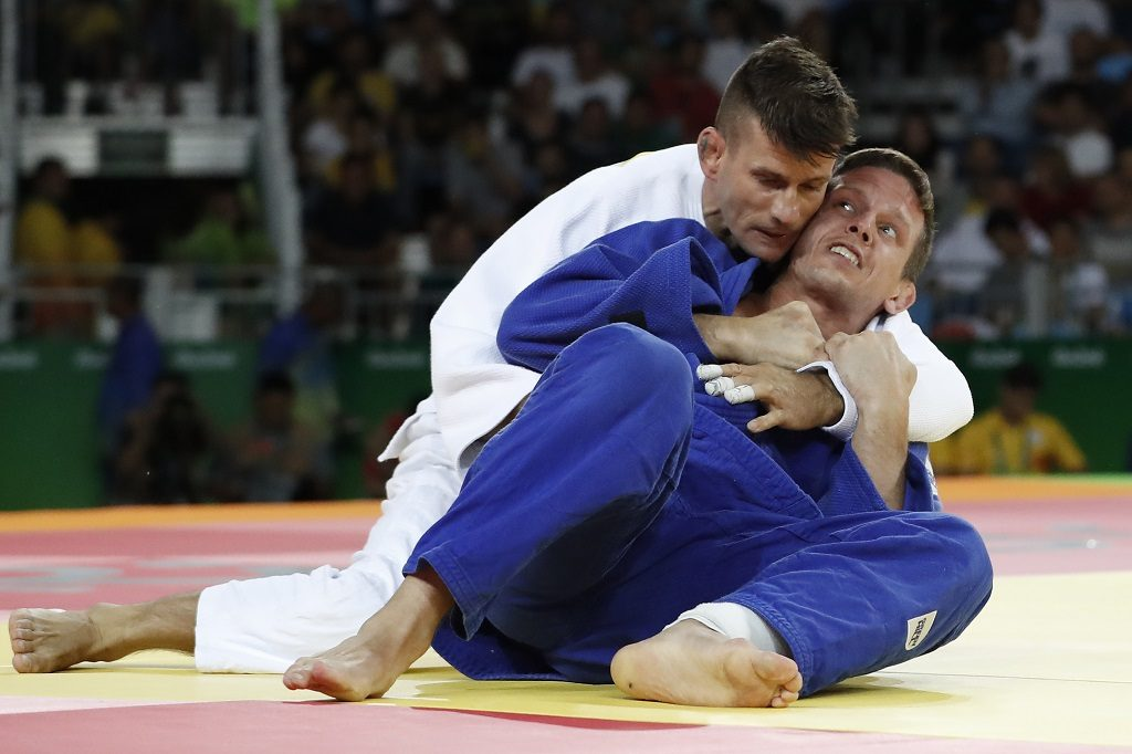 Belgium's Dirk van Tichelt (blue) competes with Hungary's Miklos Ungvari during their men's -73kg judo contest bronze medal B match of the Rio 2016 Olympic Games in Rio de Janeiro on August 8, 2016. / AFP PHOTO / Jack GUEZ