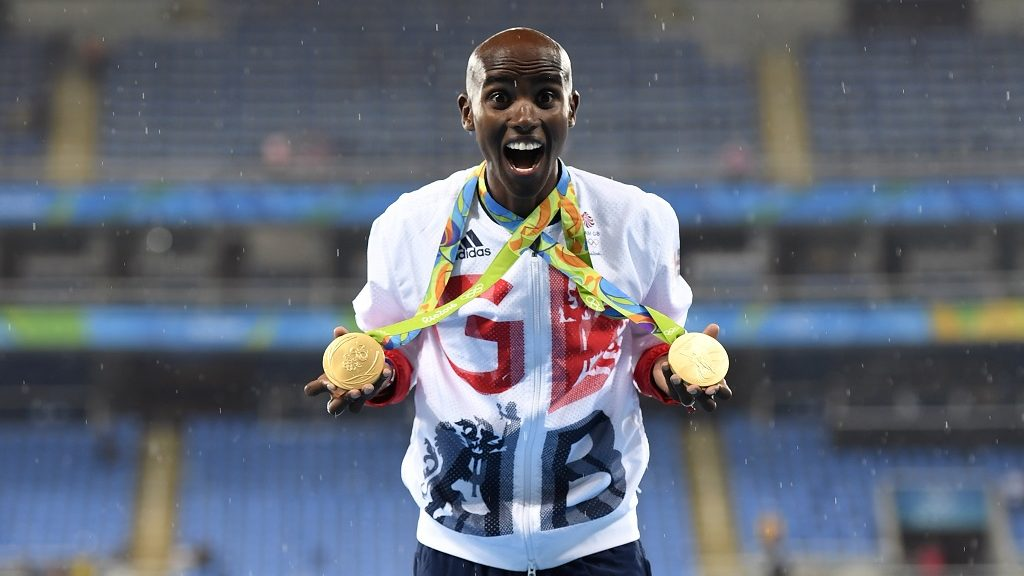 Gold medallist Britain's Mo Farah celebrates near the podium for the Men's 5000m during the athletics event at the Rio 2016 Olympic Games at the Olympic Stadium in Rio de Janeiro on August 20, 2016.   / AFP PHOTO / Eric FEFERBERG