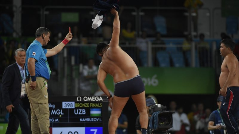 RIO DE JANEIRO, BRAZIL - AUGUST 21: Mongolian coach Bayaraa Byambarinchin strips down to his underpants in protest as fellow coach Tsogtbayar Tserenbaatar stands by shirtless after their wrestler Ganzorigiin Mandakhnaran thought he had won the bronze medal, but lost upon review to Ikhtiyor Navruzov of Uzbekistan during men's 65kg freestyle wrestling on Sunday, August 21, 2016. (Photo by AAron Ontiveroz/The Denver Post via Getty Images)