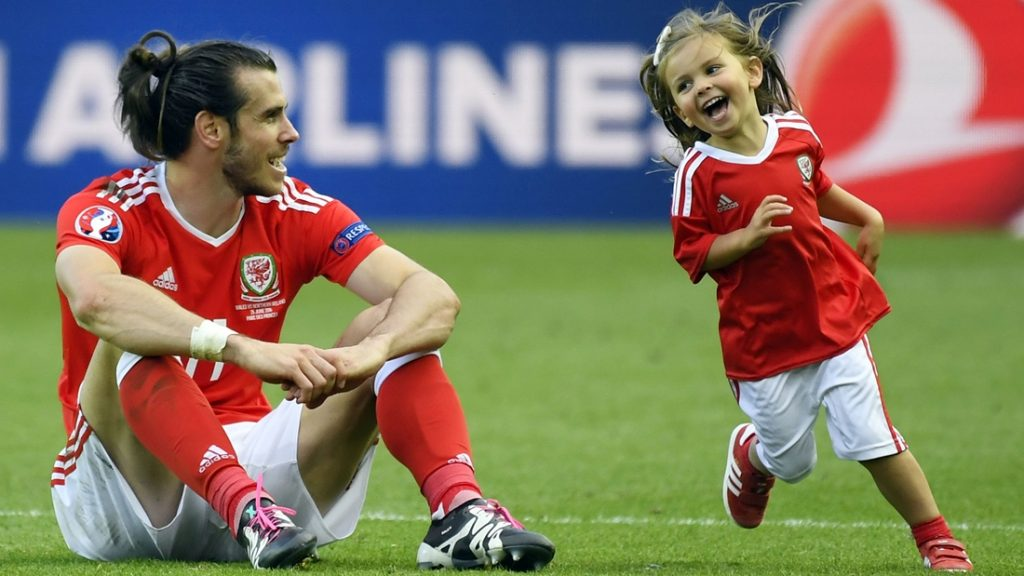 Wales' forward Gareth Bale watches his daughter Alba Viola running on the pitch following the team's 1-0 win in the Euro 2016 round of sixteen football match Wales vs Northern Ireland, on June 25, 2016 at the Parc des Princes stadium in Paris. / AFP PHOTO / DAMIEN MEYER