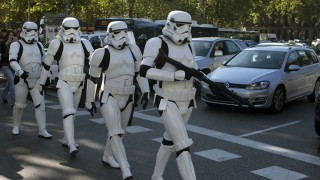 Star Wars Storm Trooper characters cross the street after a giant Star Wars helmet was unveiled, during the inauguration of an open air exhibition called 'Face the Force' in Madrid, Spain, Friday, Oct. 30, 2015. Seven other giant helmets are due to be placed in various corners in the city. (AP Photo/Paul White)  ORG XMIT: PW103