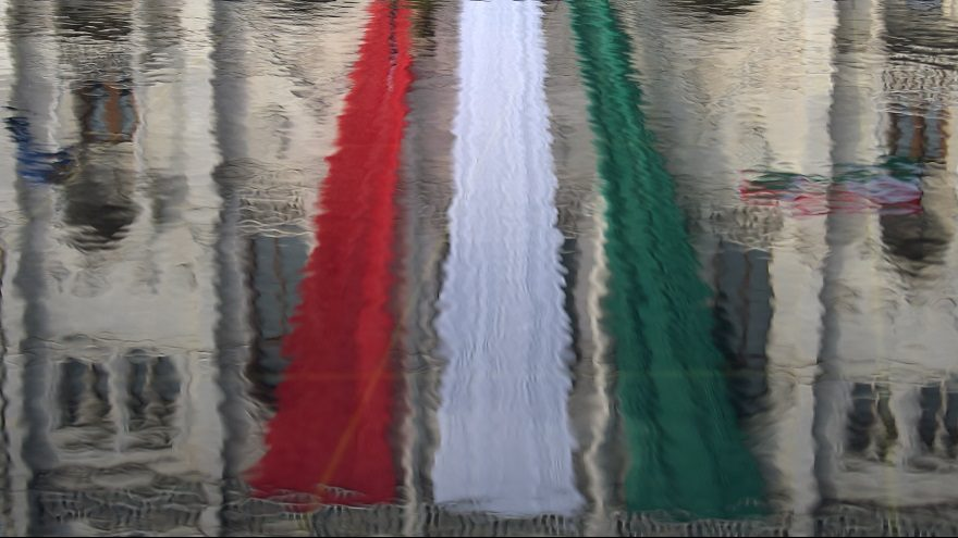 The Hungarian national flag reflects on water in front of the parliament building near the memorial of the 1956 anti-Soviet uprising, during a flag-hoisting ceremony marking the Hungary's National day in Budapest on October 23, 2015. AFP PHOTO / ATTILA KISBENEDEK / AFP PHOTO / ATTILA KISBENEDEK