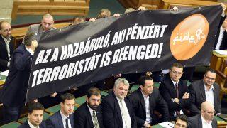 """Budapest, 2016. november 8. """"Az a hazaáruló, aki pénzért terroristát is beenged!"""" feliratú molinót tartanak az alaptörvény hetedik módosításáról szóló szavazás alatt az Országgyûlés plenáris ülésén 2016. november 8-án. 131 képviselõ szavazott igennel, 3 nemmel, így nem kapta meg a kétharmados támogatást Orbán Viktor miniszterelnök alkotmánymódosítási javaslata, amely kimondta volna, hogy Magyarországra idegen népesség nem telepíthetõ be. MTI Fotó: Kovács Tamás"""