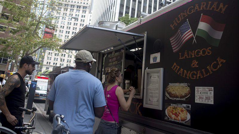 New York, 2015. július 31. A magyar Prepuk Zsolt Lángos Truckja előtt sorban állnak az emberek a New York-i Wall Streeten 2015. július 27-én. Prepuk Zsolt Magyarországon autószerelőnek tanult, majd ingatlanosként dolgozott. 1999-ben, 24 éves korában érkezett New Yorkba, ahol 14 évig éttermekben dolgozott. A nemrégiben a The New York Times című napilap gasztronómia rovata által dicsért, lángost árusító food truckot egy éve kezdte el építeni. Jelenleg a Lángos Truck a munkahelye, és két embernek ad munkát. Szintén magyar származású feleségével a napokban várják első gyermeküket.MTI Fotó: Kallos Bea