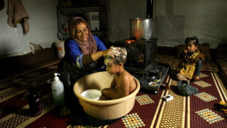 Nasser Ahmad Mustapha (C), a Syrian refugee child from the northwestern Syrian province of Idlib has his hair washed by his mother at a refugee camp in the southern Lebanese village of Ibl Al-Saki on January 7, 2015, as stormy weather continues to batter the Middle Eastern region. Many refugees in Lebanon were trapped in their tents by the heavy rain and snow, struggling to stay warm in temperatures hovering around zero degrees. AFP PHOTO / MAHMOUD ZAYYAT