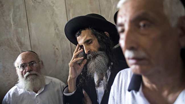 TEL AVIV, ISRAEL - MAY 27:  Orthodox Jewish men mourn during the funeral of Emanuel and Miriam Riva, who were killed in the shooting attack at the Brussels Jewish Museum this past Saturday, on May 27, 2014 in Tel Aviv, Israel. It was reported that the Rivas had traveled to Brussels on vacation and were only a few days away from returning to Tel Aviv when they were gunned down. (Photo by Ilia Yefimovich/Getty Images)