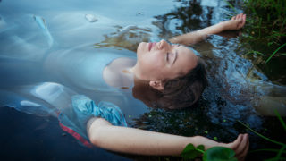 Young beautiful drowned woman lying in the river