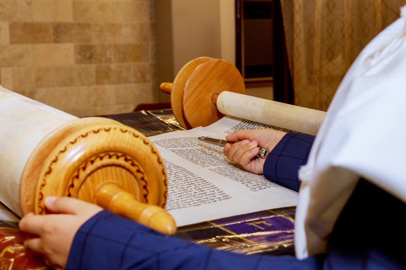 Jewish man dressed in ritual clothing Hand of boy reading the Jewish Torah at Bar Mitzvah Bar Mitzvah Torah reading