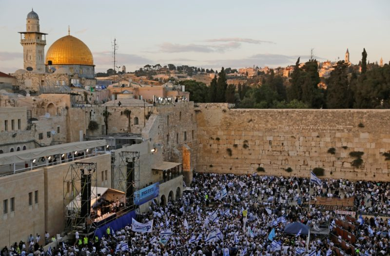 """Isreali nationalist settlers wave their national flags in front of the Western Wall in Jerusalem's Old City on May 13, 2018, as they celebrate the Jerusalem Day with the dome of the Rock in the background. For Israelis, Sunday is Jerusalem Day, an annual celebration of the """"reunification"""" of the city following the 1967 Six-Day War. / AFP PHOTO / MENAHEM KAHANA"""