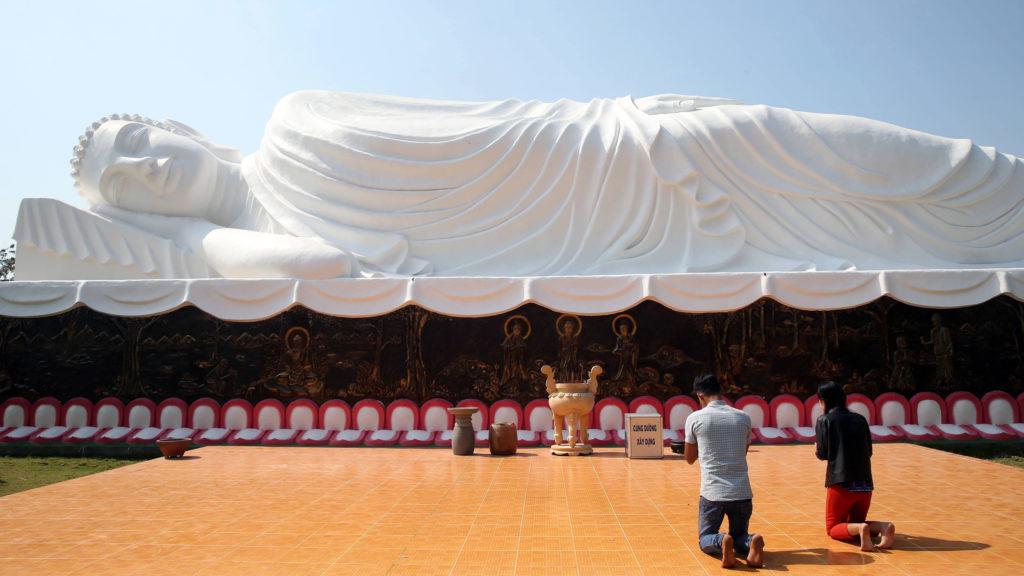 Chua Thien Lam Go buddhist pagoda.  Reclining Buddha. After 45 years of teaching the Dharma, the Buddha passed into Parinirvana. Statue.  Worshippers praying the Buddha. Thay Ninh. Vietnam.   usage worldwide