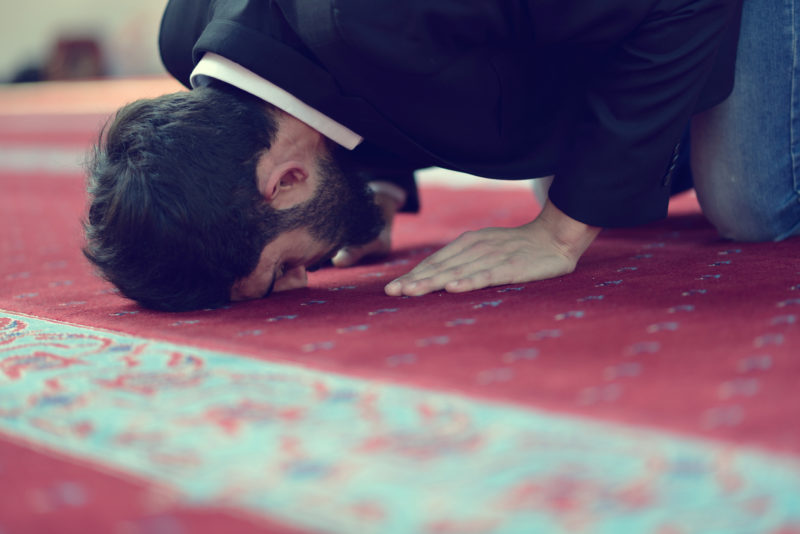 Handsome Younger Muslim Arabic man praying in mosque