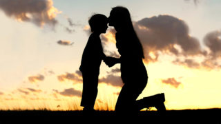 Silhouette of a young mother lovingly kissing her little child on the forehead, outside isolated in front of a sunset in the sky.
