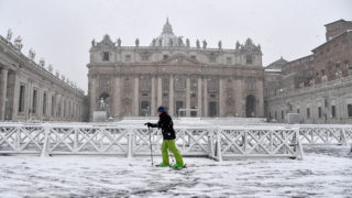 A man skis past St Peter's square covered in snow on February 26, 2018  at The Vatican    / AFP PHOTO / TIZIANA FABI