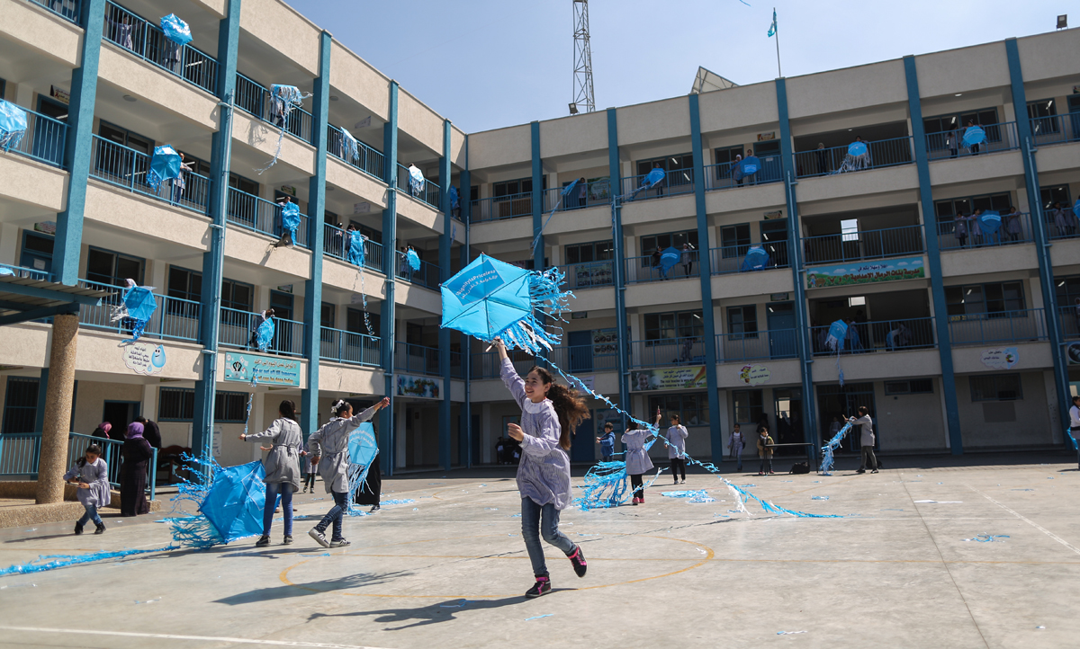 """Palestinian schoolgirls fly kites outside their classrooms at a school belonging to the United Nations Relief and Works Agency for Palestinian Refugees (UNRWA) in Gaza City on March 12, 2018 as a protest against US aid cuts.On January 16, Washington held back $65 million that had been earmarked for the UN Relief and Works Agency for Palestinian refugees (UNRWA), but the State Department denied the freeze was to punish the Palestinian leadership, which has cut ties with President Donald Trump's administration following his recognition of Jerusalem as Israel's capital last year, with a spokeswoman saying it was linked to necessary """"reform"""" of UNRWA. / AFP PHOTO / MAHMUD HAMS"""