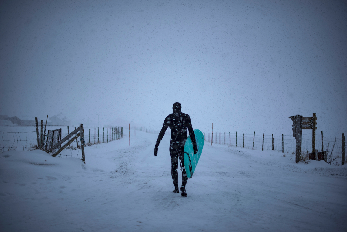 A surfer carries his surfboard as he walks out of the water under snowfall, on March 11, 2018, in Unstad, northern Norway, Lofoten islands, within the Arctic Circle. / AFP PHOTO / OLIVIER MORIN