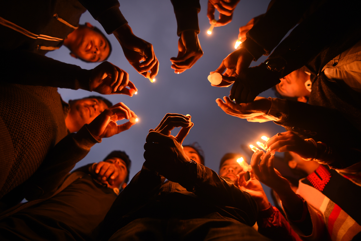 Nepali people take part in a candlelight vigil in honour of the plane crash victims in Kathmandu on March 13, 2018, a day after the deadly crash of a US-Bangla Airlines plane at the international airport. At least 49 people were killed and 22 injured when a Bangladeshi plane crashed and burst into flames near Kathmandu airport on March 12, in the worst aviation disaster to hit Nepal in years. Officials said there were 71 people on board the US-Bangla Airlines plane from Dhaka when it crashed into a field near the airport. / AFP PHOTO / PRAKASH MATHEMA