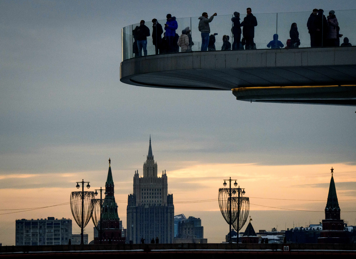 People enjoy the view from a pedestrian bridge in the Zaryadye Park, with the Kremlin's towers and the Russian Foreign Ministry headquarters seen in the background, in Moscow on March 13, 2018.The Russian Foreign ministry said on March 13, 2018 it had summoned the British ambassador amid an escalating row over the poisoning of a former double agent. / AFP PHOTO / Mladen ANTONOV