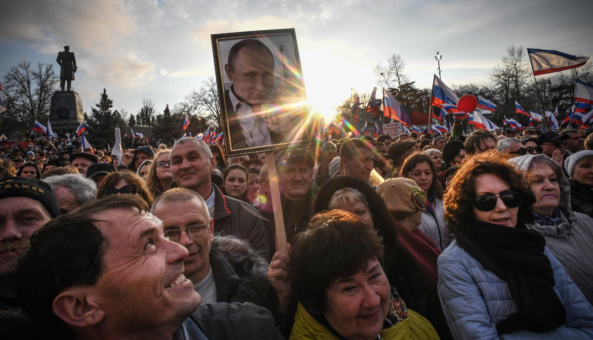 Supporters of Russian President Vladimir Putin gather for a rally to celebrate the fourth anniversary of Russia's annexation of Crimea at Sevastopol's Nakhimov Square on March 14, 2018.Russia will vote for President on March 18, 2018. / AFP PHOTO / Yuri KADOBNOV