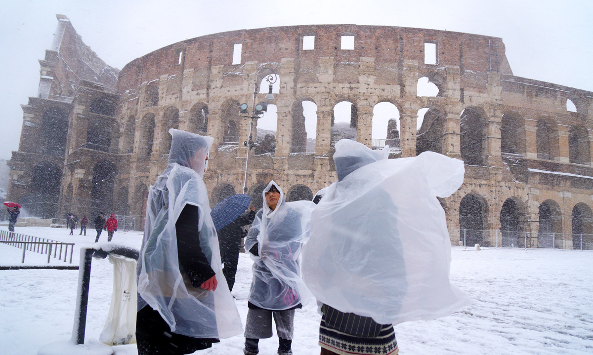 Japanese tourists put plastic coats as they visit the ancient Colosseum during a snowfall in Rome on February 26, 2018.     / AFP PHOTO / Vincenzo PINTO