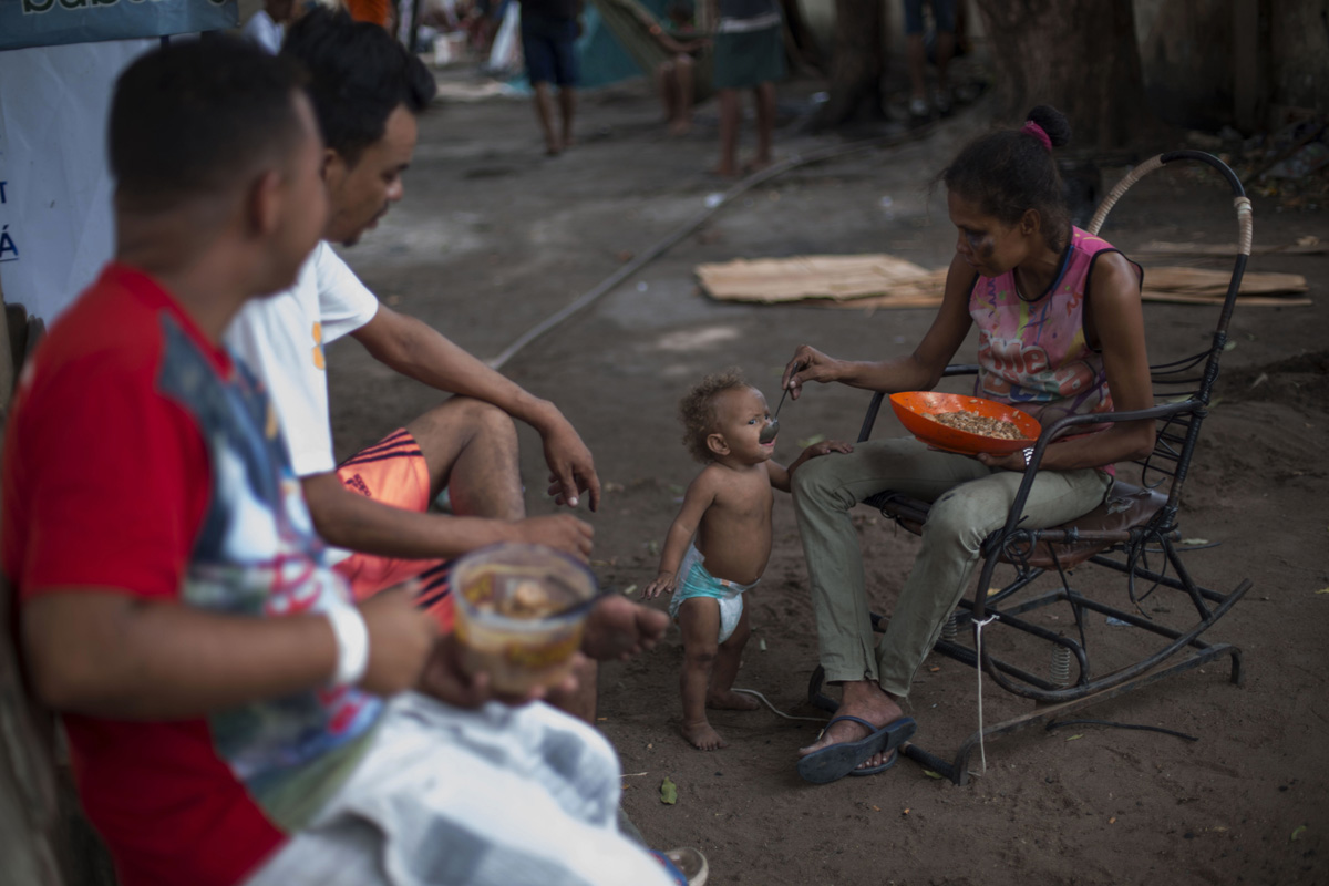 A Venezuelan refugee feeds her son, at Tancredo Neves shelter in the city of Boa Vista, Roraima, Brazil, on February 24, 2018. When the Venezuelan migratory flow exploded in 2017 the city of Boa Vista, the capital of Roraima, 200 kilometres from the Venezuelan border, began to organise shelters as people started to settle in squares, parks and corners of this city of 330,000 inhabitants of which 10 percent is now Venezuelan.  / AFP PHOTO / MAURO PIMENTEL