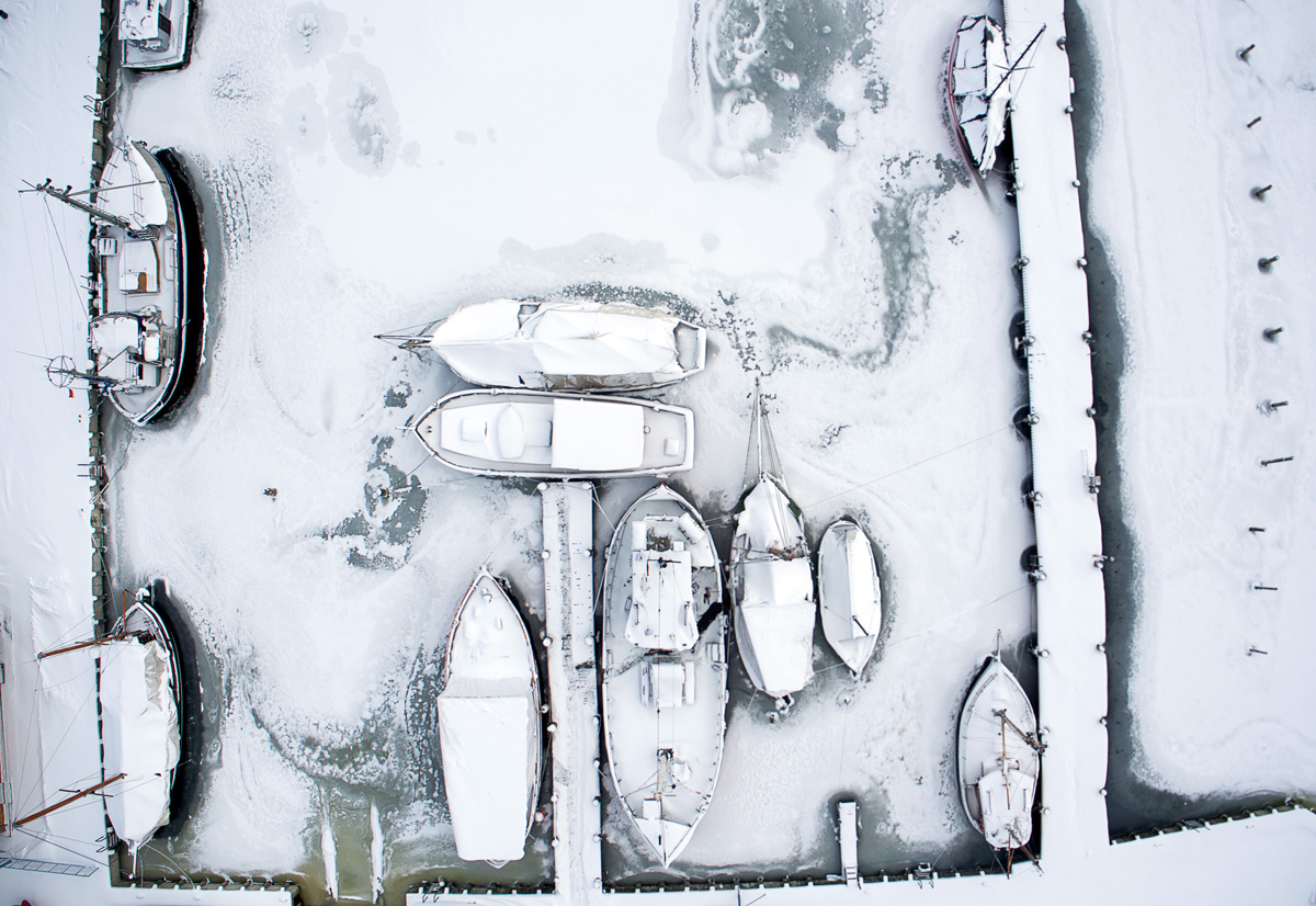 """Picture taken with a drone shows snow-covered sailing ships mooring at the boatyard harbour of Kirchdorf on the Baltic Sea island of Poel, northeastern Germany, where bays risk to freeze due to permafrost and night temperatures below minus ten degrees Celsius, on February 27, 2018.A blast of Siberian weather dubbed """"The Beast from the East"""" sent temperatures plunging across much of Europe. / AFP PHOTO / dpa / Jens Büttner / Germany OUT"""