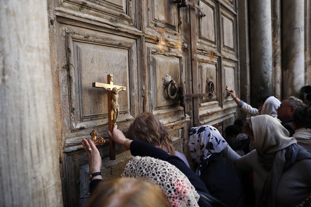 Pilgrims pray outside the closed gate of the Church of the Holy Sepulchre in Jerusalem's Old City on February 27, 2018.The church in Jerusalem built at the traditional site of Jesus's burial remained closed for a third day as Christian leaders protested against Israeli tax measures and a controversial proposed law. / AFP PHOTO / Thomas COEX