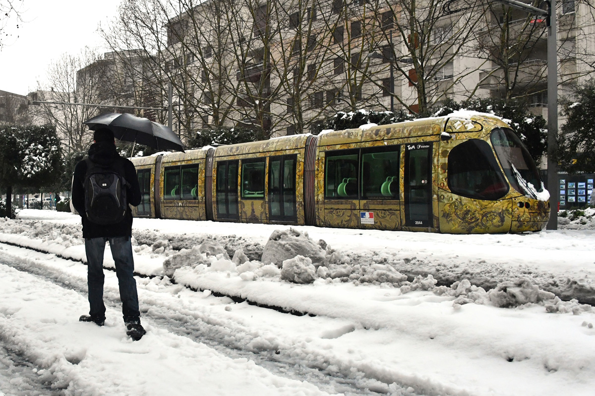 A man walks on a snow covered road past a tramway blocked by snow on March 1, 2018 in Montpellier, southern France, after heavy snow fall.Fresh heavy snowfalls and icy blizzards were expected to lash Europe on March 1 as the region shivers in a deadly deep-freeze that has gripped countries from the far north to the Mediterranean south. / AFP PHOTO / PASCAL GUYOT