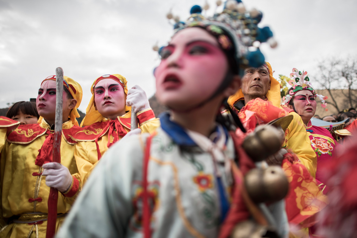 This picture taken on February 27, 2018 shows villagers dressed in traditional costume as they prepare to perform during the She Huo festival in Longxian, Shaanxi province.Villagers in northern China wake up before dawn to paint their faces with pinkish make-up, don colourful robes and wield swords to represent legendary figures for the She Huo festival, a unique event capping Chinese New Year celebrations. / AFP PHOTO / Fred DUFOUR