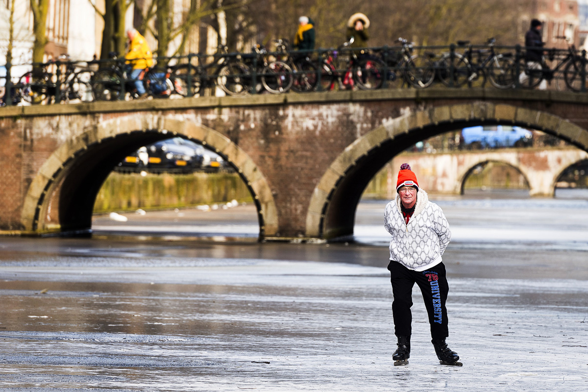 A skater skates on the ice of the lightly frozen Keizersgracht Canal in Amsterdam on March 1, 2018. Heavy snowfall and deadly blizzards lashed Europe, forcing airports to cancel or delay flights around the continent, as a deep freeze gripped countries from the far north to the Mediterranean beaches in the south. / AFP PHOTO / ANP / Evert Elzinga / Netherlands OUT
