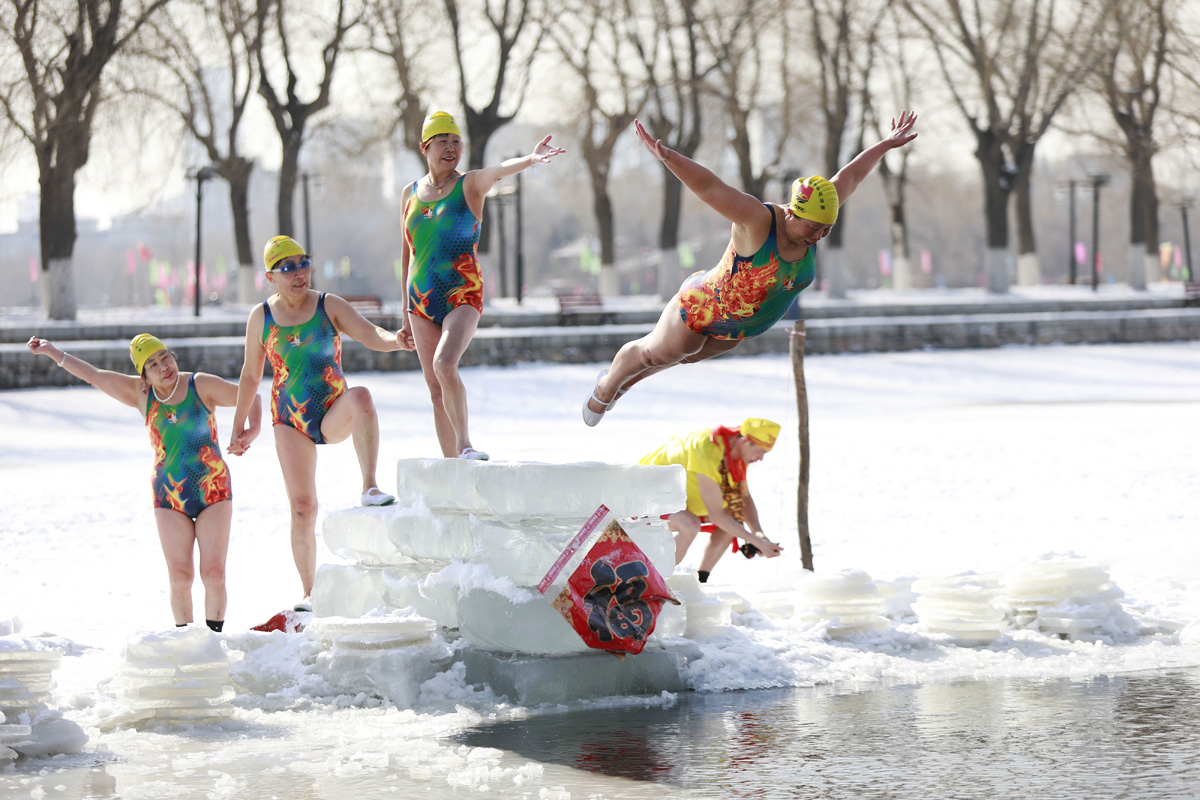 A woman dives into a partly frozen lake in Shenyang in China's northeastern Liaoning province on March 2, 2018. / AFP PHOTO / - / China OUT