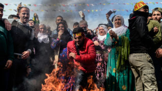 A man jumps over a bonfire during a Kurdish celebration of Nowruz (aka Noruz or Newroz), the Persian calendar New Year, in Istanbul on March 21, 2018. / AFP PHOTO / YASIN AKGUL