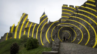 Tourists visit the medieval city of Carcassonne on April 23, 2018, whose walls are partly covered with yellow concentric circles created by the Paris-based, Swiss artist  Felice Varini at the request of the National Center for National Monuments to celebrate the twentieth anniversary of the inscription of the city as UNESCO World Heritage. / AFP PHOTO / ERIC CABANIS / RESTRICTED TO EDITORIAL USE - MANDATORY MENTION OF THE ARTIST UPON PUBLICATION - TO ILLUSTRATE THE EVENT AS SPECIFIED IN THE CAPTION