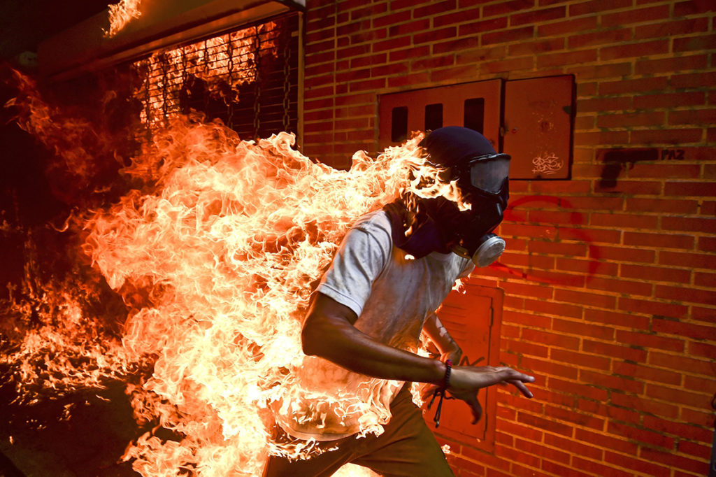 Caracas, 2018. április 13.Ronaldo Schemidtnek, az AFP francia hírügynökség Venezuelában született, Mexikóban élő fotóriporterének a képe, amely elnyerte a World Press Photo nemzetközi sajtófotóverseny fődíját, az Év Sajtófotója díjat, valamint a hírkép egyedi kategória első díját 2018. április 12-én. A 2017. május 3-án készült felvételen a Nicolás Maduro venezuelai elnök alkotmánymódosítási törekvéseit ellenző tüntetők egyike, a 28 éves Jose Victor Salazar Balza fut égő ruhában a rohamrendőrökkel történt összecsapások közben Caracasban. (MTI/EPA/World Press Photo/Ronaldo Schemidt)