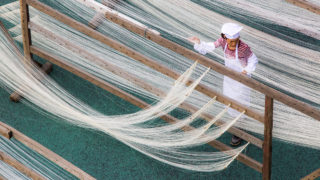 This photo taken on April 21, 2018 shows a woman making traditional hand-made noodles during a working skills competition in Fuzhou in China's Fujian province. / AFP PHOTO / - / China OUT
