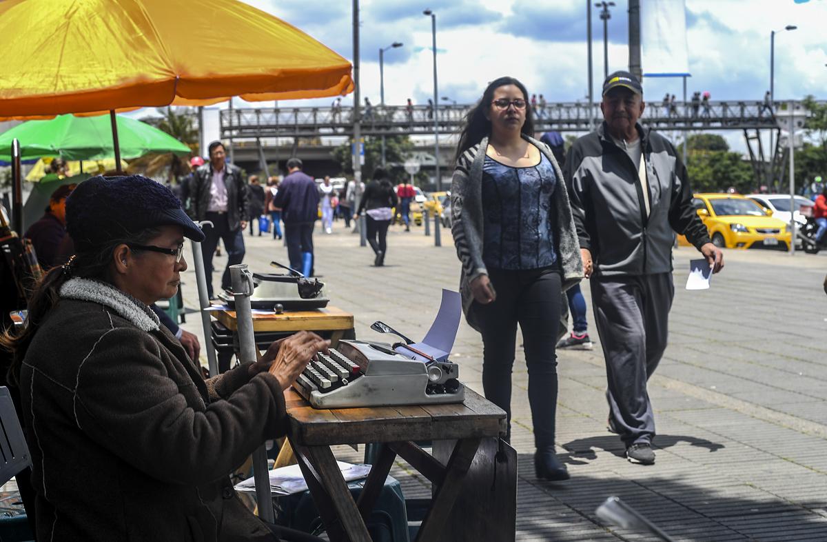 Candelaria Pinilla egy levelet gépel a bogotai adóhivatallal szemben. Bogotában több Pinillához hasonló ember dolgozik az utcán, pénzért segítenek adózási és egyébb papirmunka kitöltésébenFotó: Luis Acosta / AFP