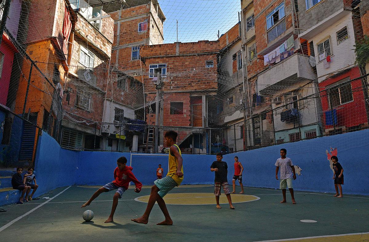 Boys play football on a pitch at Tavares Bastos favela in Rio de Janeiro, Brazil, on May 27, 2018. / AFP PHOTO / Carl DE SOUZA