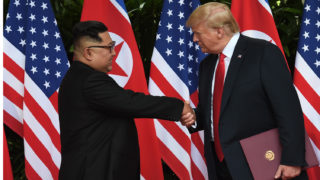 North Korea's leader Kim Jong Un (L) shakes hands with US President Donald Trump (R) after taking part in a signing ceremony at the end of their historic US-North Korea summit, at the Capella Hotel on Sentosa island in Singapore on June 12, 2018.Donald Trump and Kim Jong Un became on June 12 the first sitting US and North Korean leaders to meet, shake hands and negotiate to end a decades-old nuclear stand-off. / AFP PHOTO / POOL / Anthony WALLACE
