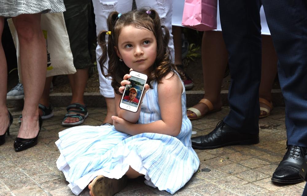 A négyéves Luciana Villavicencio mutatja apja, Pablo Villavicencio fényképét a kislány anyjával tartott sajtótájékoztatón New Yorkban 2018. június 18-án. Az ecuadori állampogárságú apát a bevándorlásügyi hatóság vette őrzetbe az elmúlt hetekben, miután egy rutinellenőrzés alkalmával felfedezték, hogy a férfi 2009 óta engedély nélkül tartózkodik az országban.AFP PHOTO / TIMOTHY A. CLARY