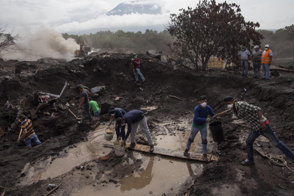 San Miguel Los Lotes, 2018. június 18. Önkéntesek és hozzátartozók kutatnak áldozatok holtteste és esetleges túlélõk után a Fuego tûzhányó kitörése nyomán vulkáni hamuval borított dél-guatemalai San Miguel Los Lotes településen 2018. június 17-én. A június 3-án bekövetkezett természeti katasztrófa halálos áldozatainak száma 110 fölé emelkedett. Eddig közel 12000 embert menekítettek ki a vulkánhoz közeli településekrõl. (MTI/AP/Rodrigo Abd)