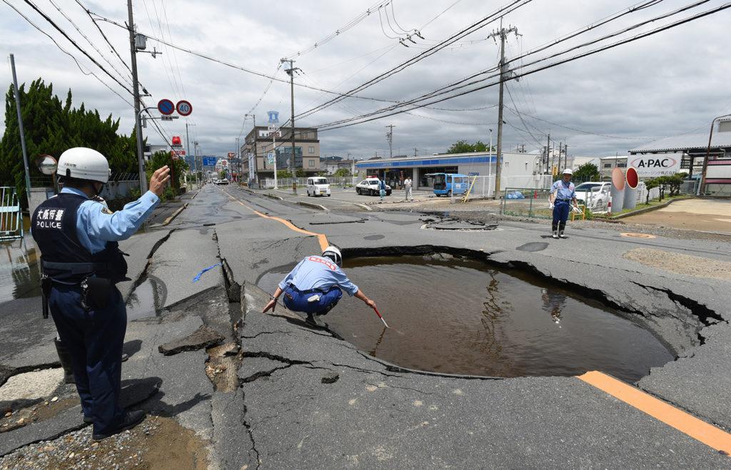 Oszaka, 2018. június 18.Óriási, vízzel teli kráter keletkezett egy megrongált úttesten Oszakában 2018. június 18-án, miután 6,1-es fokozatú földrengés rázta meg Japán nyugati térségét. A természeti csapásban három ember életét vesztette, és több mint kétszázan megsérültek. A rengés központja az oszakai prefektúra északi részén, mintegy 13 kilométeres mélységben volt. (MTI/EPA/Jiji Press)