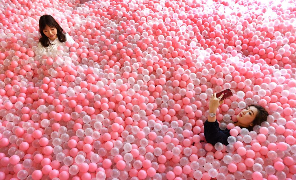 A Sugar Republic névre keresztelt, édességekről szóló pop-up múzeum látogatói szelfiznek egy cukorkákra emlékeztető labdákkal teli medencében. Fotó: AFP / William West