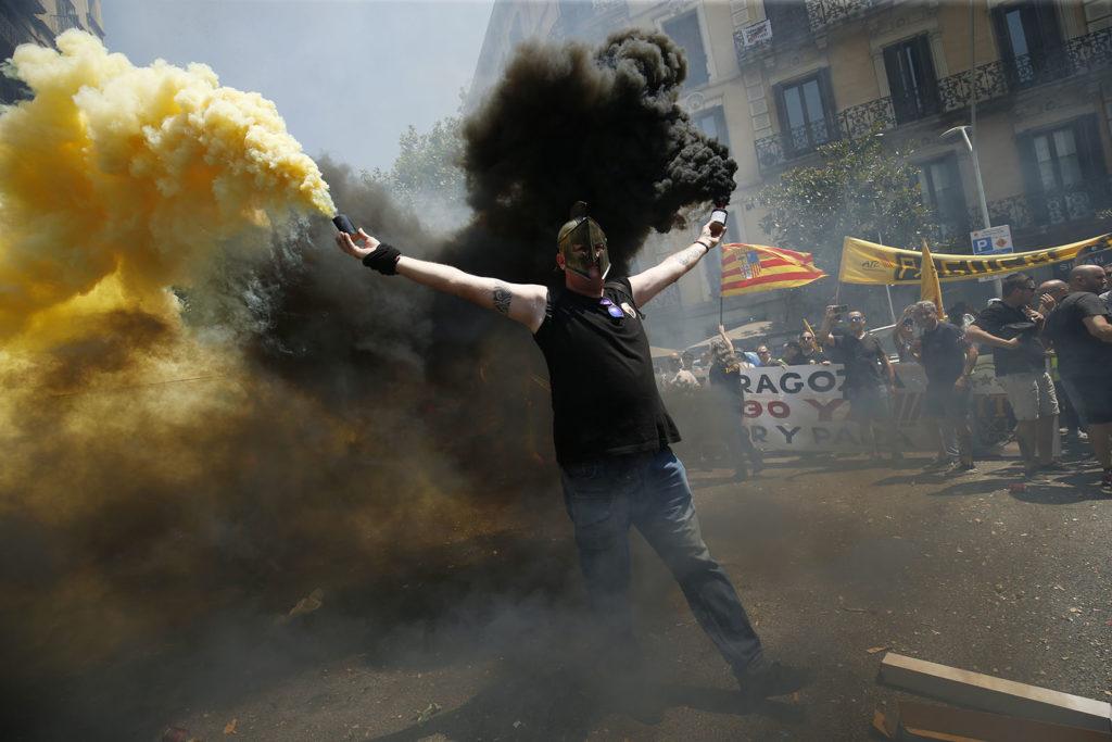 Taxisofőr füstgránátokkal a barcelonai taxisok sztájkján. Fotó: AFP / Pau Barrena