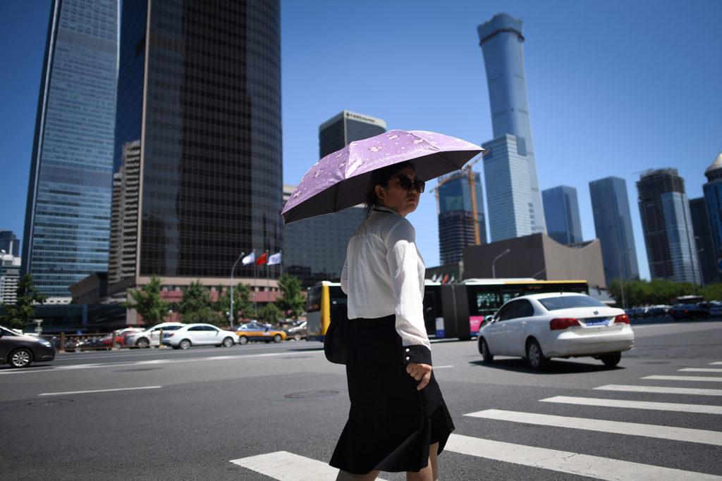 Napernyős nő kel át a zebrán Peking üzleti negyedébe. Fotó: AFP / WANG ZHAO